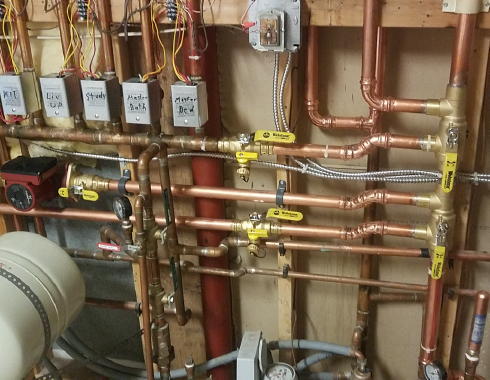 organized copper pipes on the wall in mechanical room