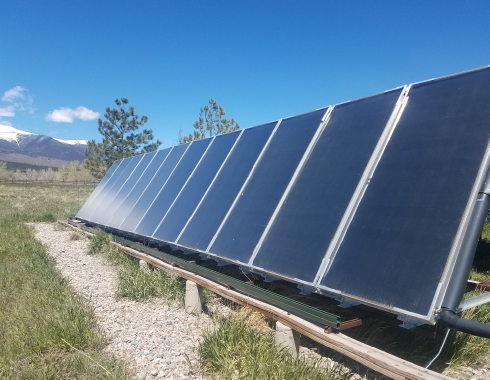 newly installed row of solar panels on the ground with mountains in the background