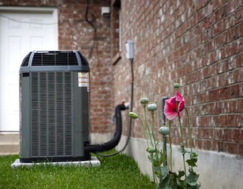 outdoor air conditioning unit next to a pink flower
